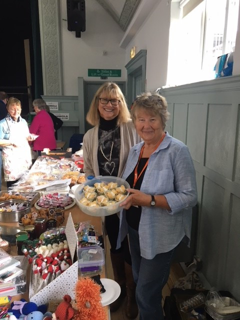 Alison Spencer is holding a box of cakes. She is stood bby a table of cakes. Behind her is fellow volunteer Carol