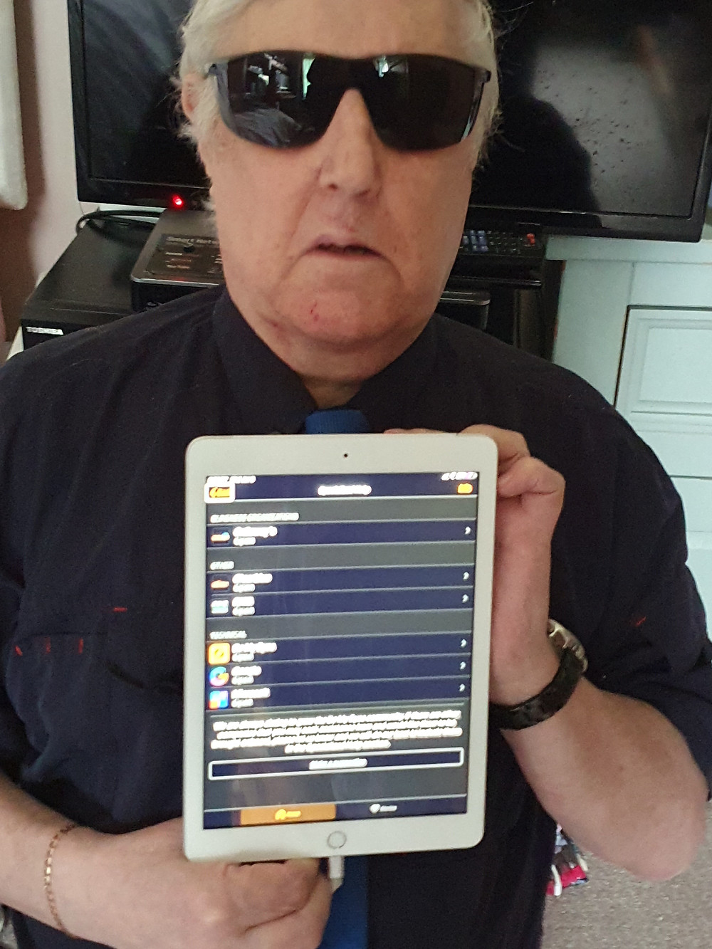 Photo shows David, wearing dark glasses, holding up a Tablet. He has the Be My Eyes menu on the screen