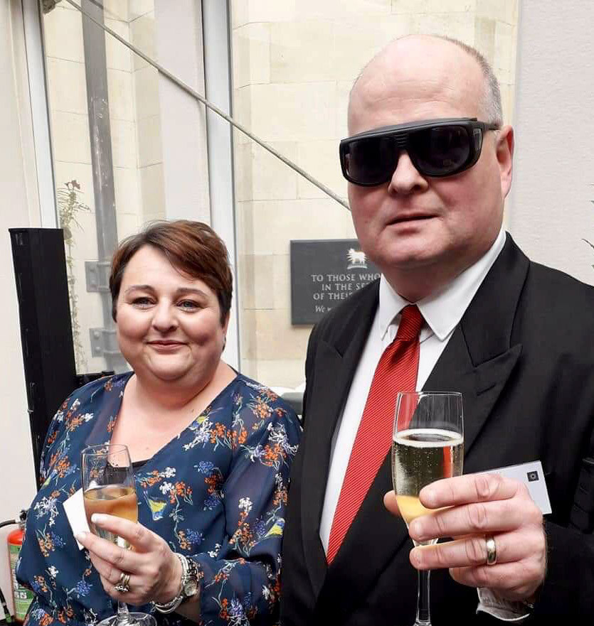 Penny and Nigel are holding up glasses of Prosecco. Penny is wearing a dark blue dress with flowers. Nigel is wearing a white shirt, red tie, black jacket and dark glasses.