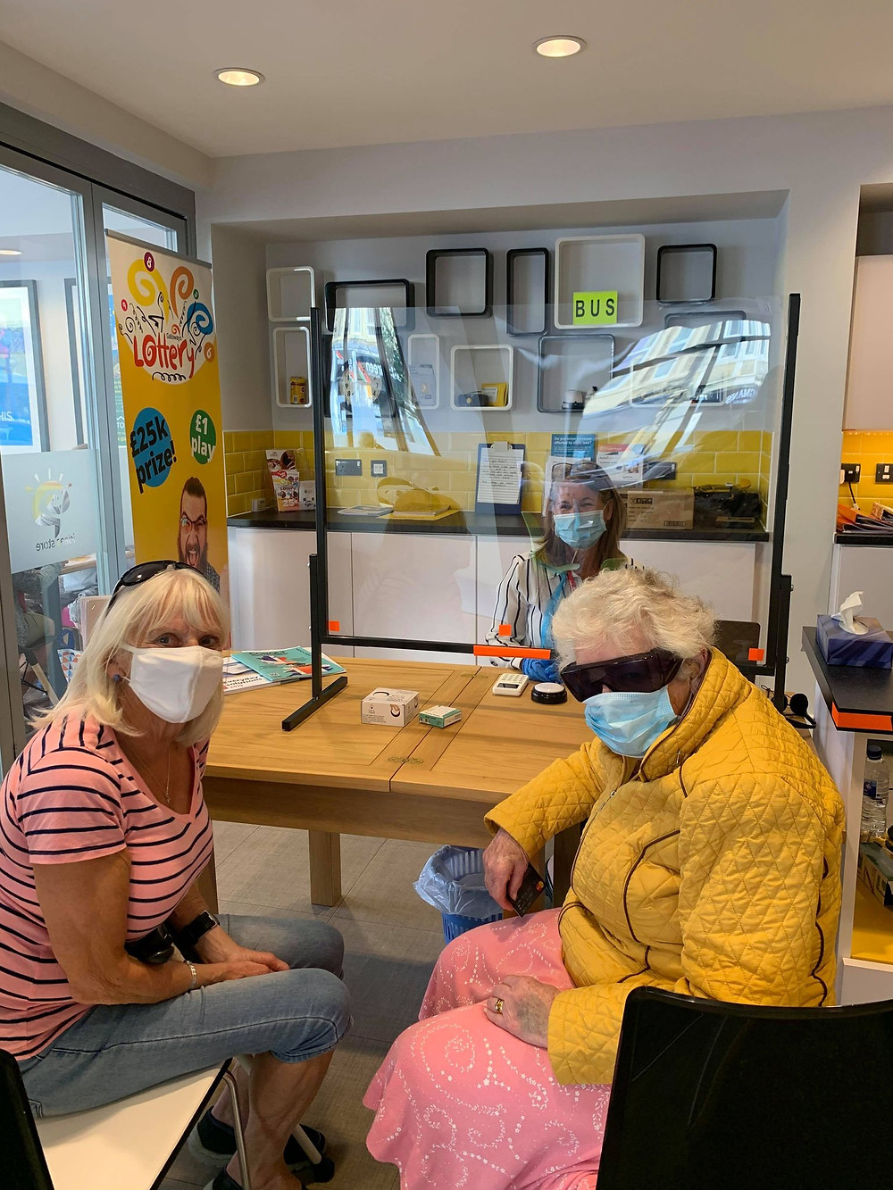 Photo shows Pam sat behind a safety screen which is on a table. In front of the screen are two women, One is wearing dark glasses. All three are wearing face masks. They are sat in the Ideas Store in Morecambe.