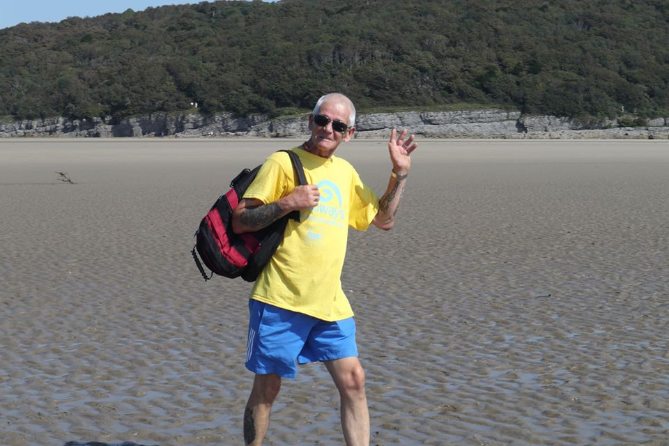 Photo shows Terry Hazell ewarng a yellow Galloway's Morecambe Bay Walk T-shirt and a black backpack. He is stood on his own on the sands of Morecambe Bay