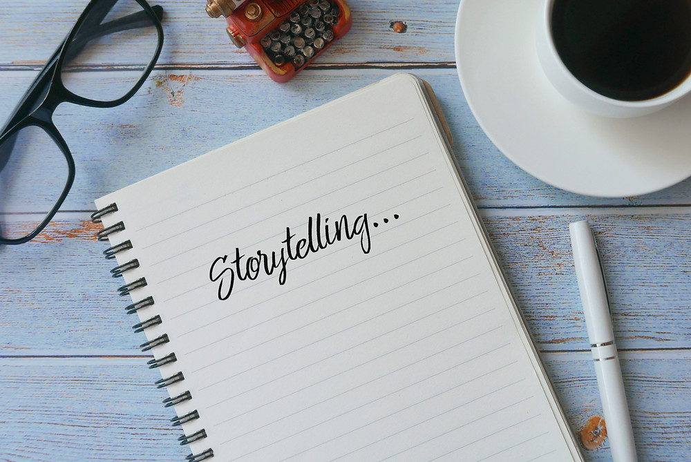 Image shows a notepad with the words storytelling on a table. There is also a pair of glasses, a cup of coffee and a pen