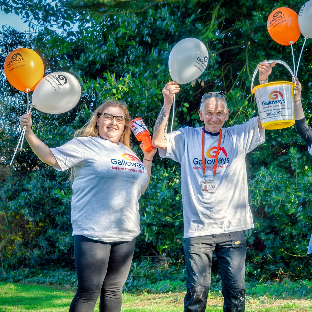 Photo shows Charlotte and Terry wearing white Galloway's T-shirts and holding orange and white Galloway's balloons. Charlotte is also holding an orange collection  tin and Terry is holding a yellow collection bucket