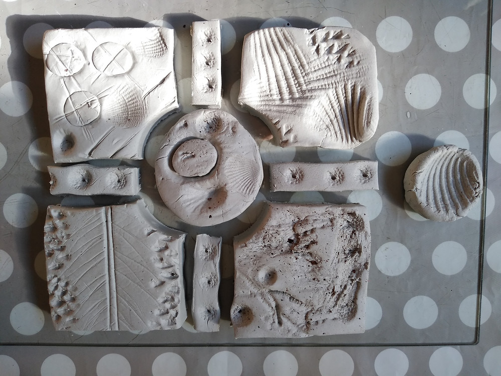 Photo shows clay work created by Jonathan. There are four squares with different imprint patterns.  These are separated by a circle and four thing rectangles in the shape of a cross.