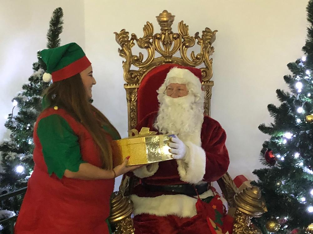 Elf Charlotte gives Santa a shiny new present