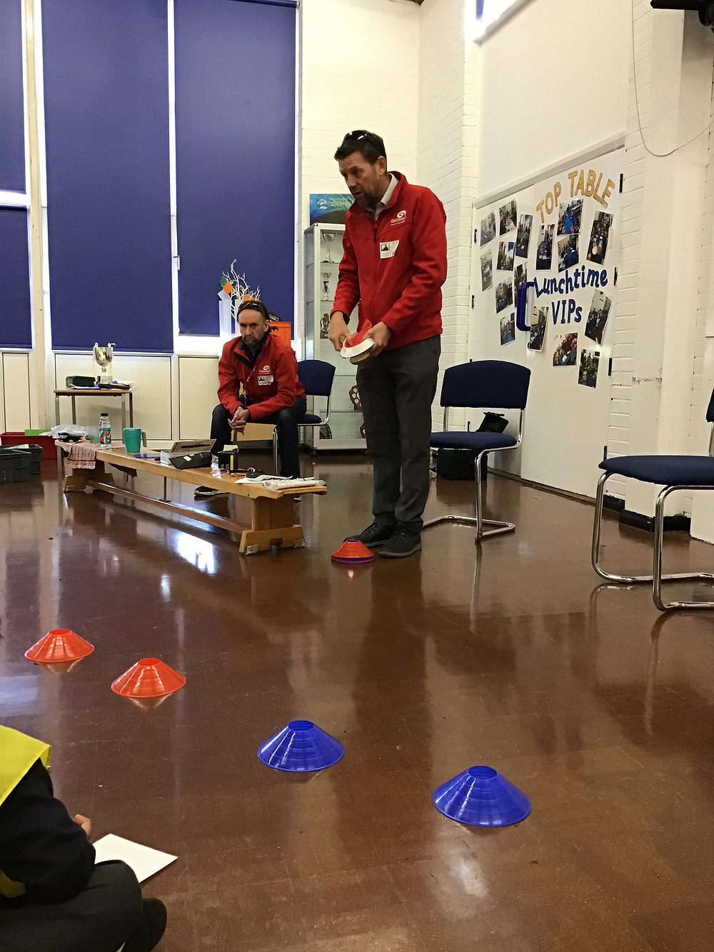 Photo shows Stuart (standing) and James (sitting) at the front of the assembly hall. Stuart is demonstrating a piece of equipment. To the left of him is a bench, with visual tools. Stuart is stood behind a red cone. There are also red and blue cones 2m in front of him.