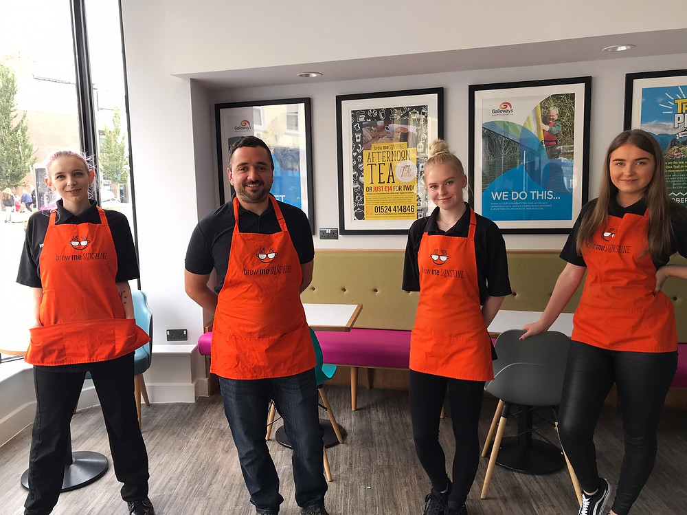 Photo shows four Brew Me Sunshine staff wearing black clothing and orange aprons stood socially distanced in a line in the cafe. Joseph Gardiner, cafe manager, is second left. The rest are female staff. The window is on their left. Behind them are tables and chairs and on the wall are giant posters advertising Galloway's activities and services.
