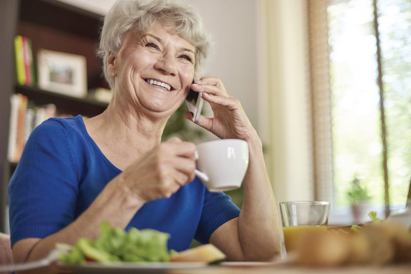 Photo shows an older woman holding a cup of coffee having a chat on the phone, She is smiling