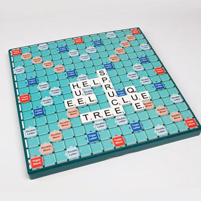 Photo shows a blue large print  Scrabble board, The letter spell out tree, help, eel, spruce, clue, que and hue