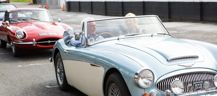 Image shows two people sat in a blue and white classic car, with a red classic car behind them