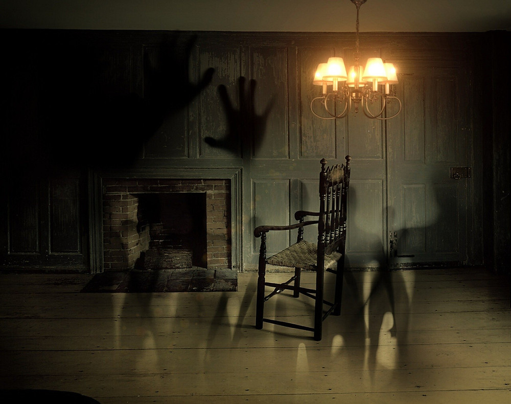 Photo shows a dark room with a chair facing a hollow fireplace. A light is hanging above. There are shadows surrounding the chair and on the wall