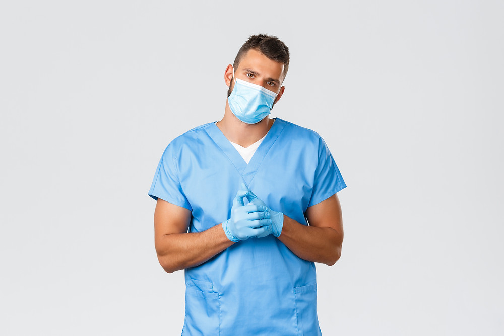 A male nurse is wearing blue scrubs, a mask and gloves