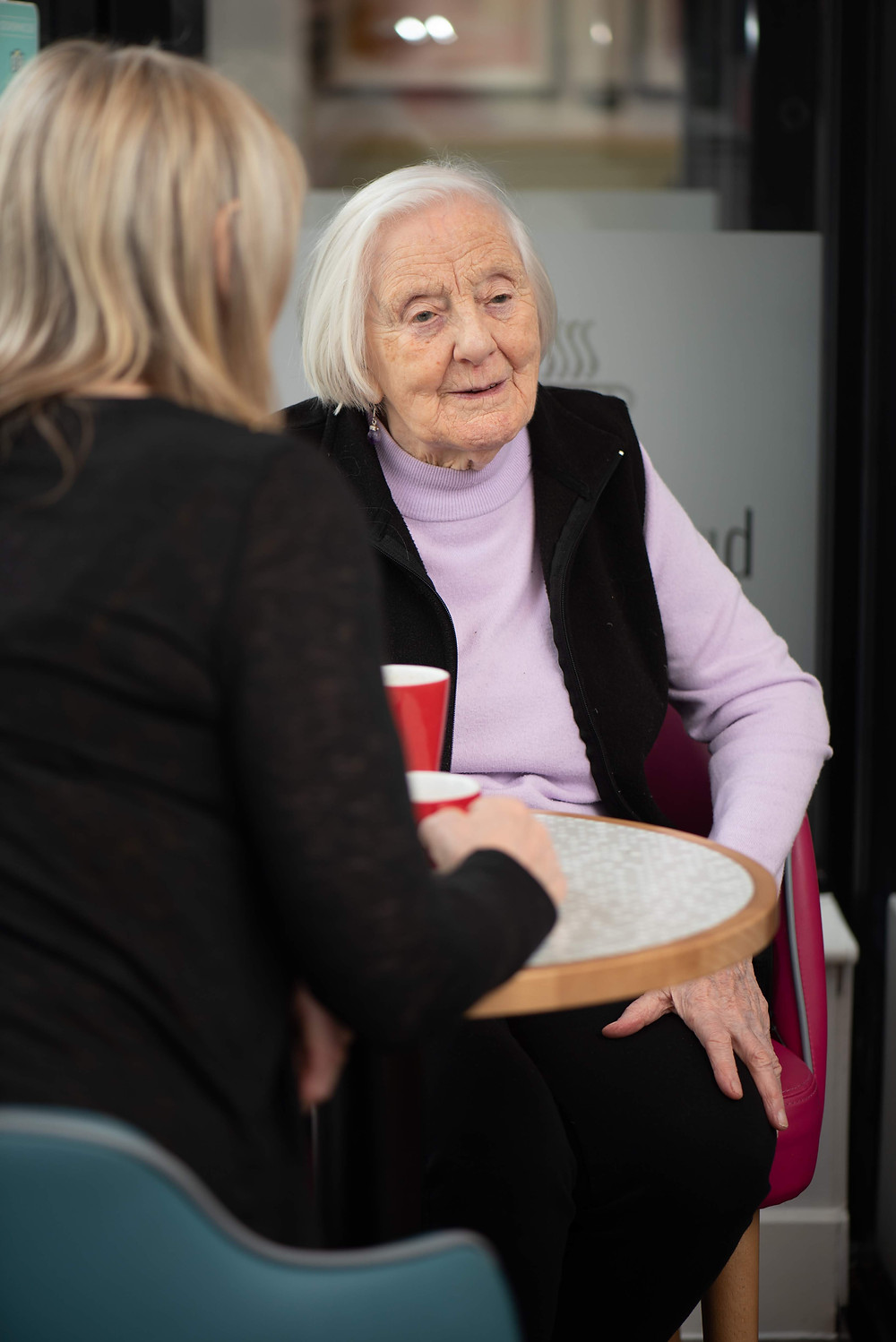 Photo shows an older lady sat in the Brew Me Sunshine cafe with a younger woman.