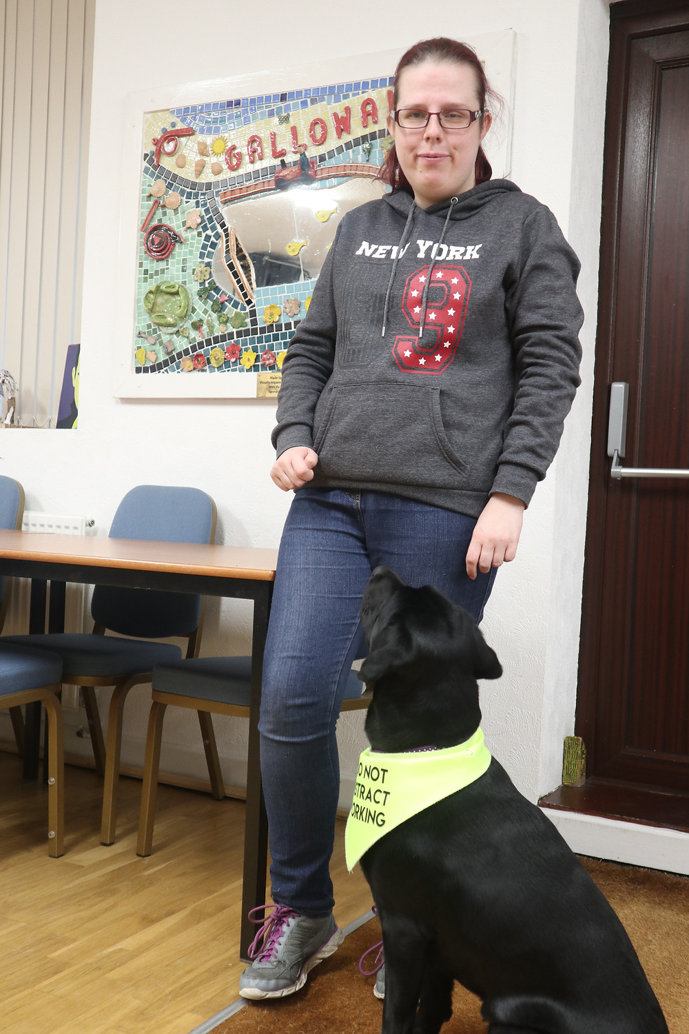 Helen Colson stood up with her guide dog Kelly. Kelly is wearing a fluorescent yellow vest. Behind them is a mosaic created by the art group