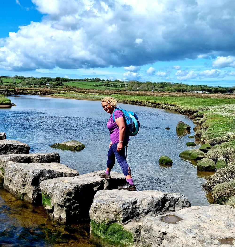Ruth is walking on large flat rocks across the water