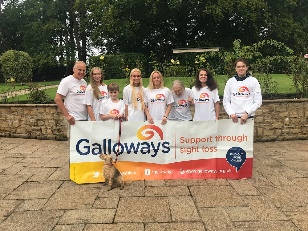 Photo shows Simon, Grace, Arthur (with Margot the dog) Mavis, Jill and Harry stood on paving holding a Galloway's banner. Behind them is the garden wall and a large lawn, yellow roses, hedges and tall trees