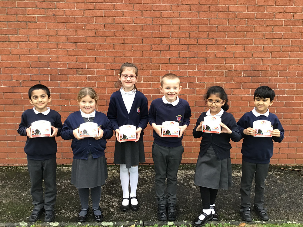 Photo shows 6 pupils wearing navy blue stood in a line facing the camera, smiling and holding their collection boxes