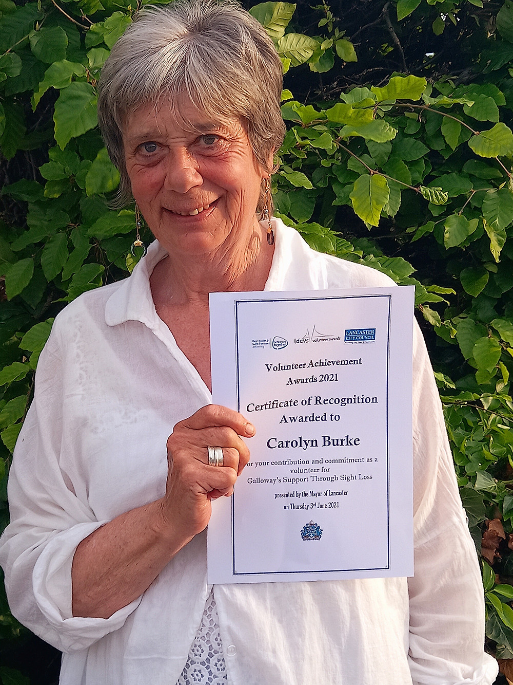 Carolyn is wearing a white shirt and is holding her certificate. She is stood in front of a bush