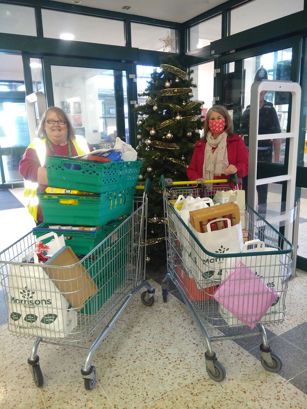 Photo shows Karen, left, and Pam, right, stood behind a trolley each, filled with Morrisons bags full of items. Behind them is a Christmas tree. They are stood in the entrance way at Morrisons in Morecambe.