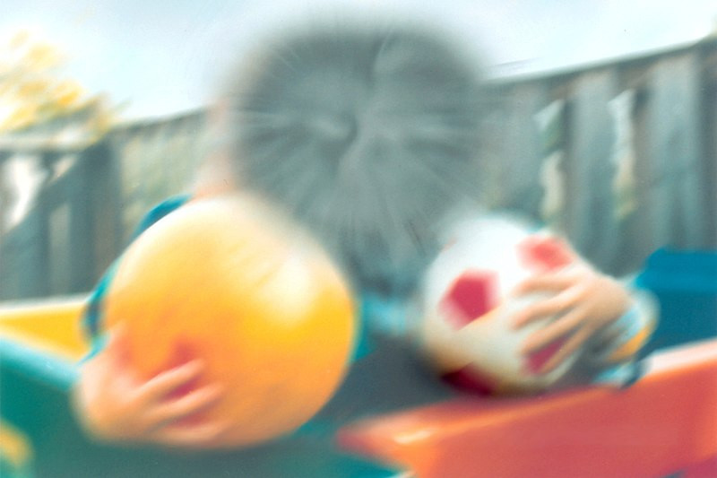 Photo shows a blurred picture of a boy holding two balls. There is a black blur covering his face