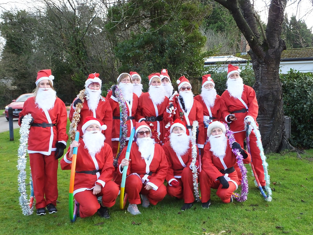 Photo shows 13 Santas lined up on grass outside Howick House. Four are kneeling, the rest are standing. They are holding hula hoops