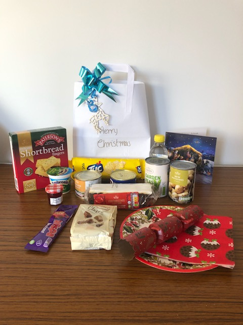 Photo shows the decorated bag with the items: lemonade, shortbread, chocolate, tinned meat, tinned vegetables, jam, Christmas cake, a Christmas card, cracker and festive paper plate and napkin