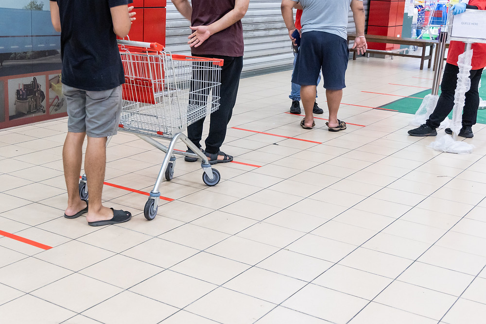 Photo shows people queuing at a supermarket with trolleys. There are markings 2m apart on the floor.