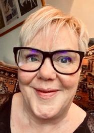 Head shot of Elizabeth Wainwright. She has short blonde hair and is wearing black rimmed glasses
