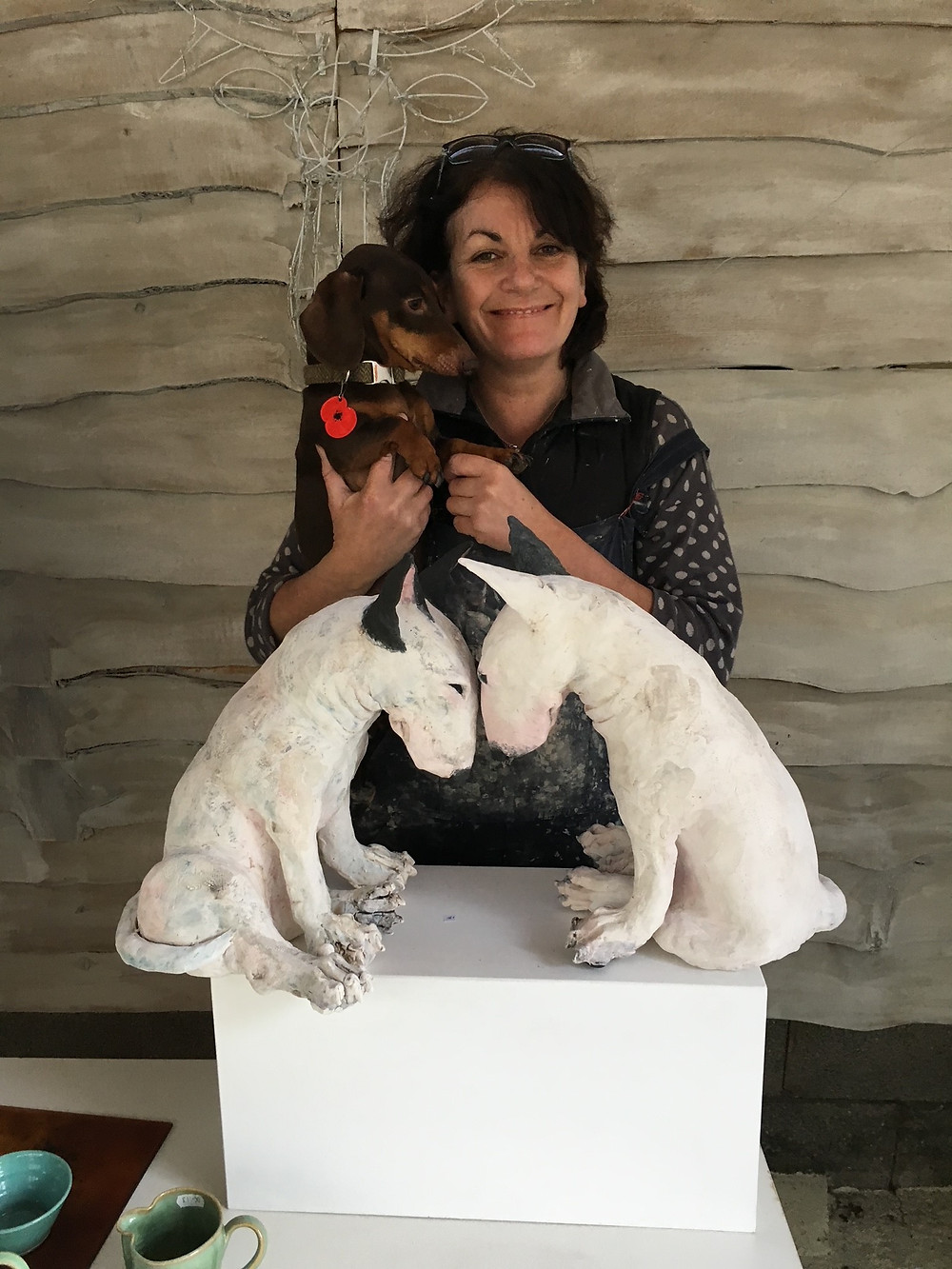 Photo shows Christine holding her daxie dog Frank. In front of her is a white plinth with two large white ceramic dogs facing each other