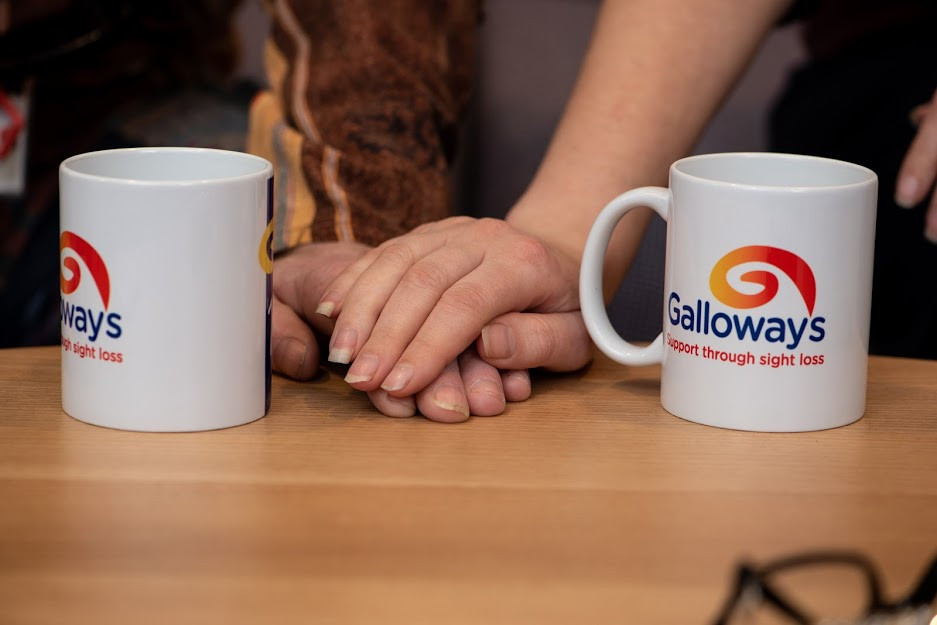 Photo shows someone putting their hand over another's hand, showing support. Their hands are on the table, in between two Galloway's mugs