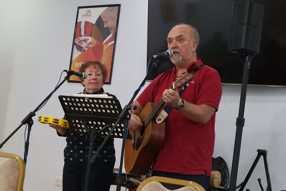 Bernadette Dixon on the left holding a yellow tambourine with Graham Dixon holding the guitar. Both have microphones in front of them and a music stand.They are performing at Galloway's in Penwortham