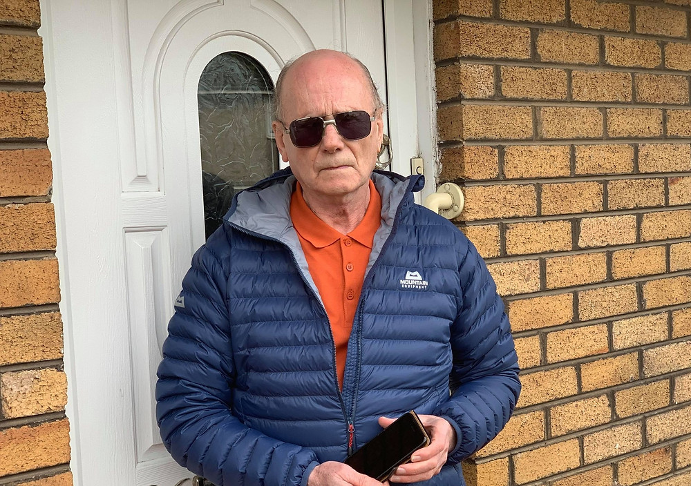 Photo shows Graham Ross holding his iPhone. He is stood outside his house and is wearing dark glasses and a blue coat