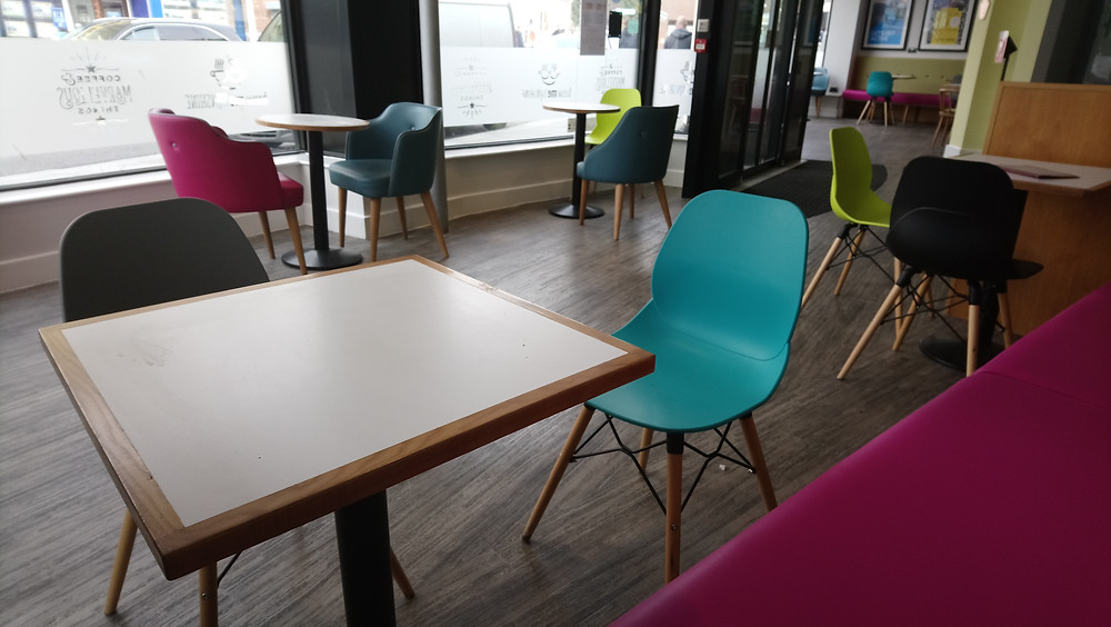 Photo shows a square table in the foreground with a grey and light blue chair. To the right is a square table with a grey and light green chair. Behind is a circular table with a pink and grey chair.To the right of that is another circular table 2m away, with a lime green and grey chair. These two tables are by the window. To the far right are adjoining doors to the other part of the cafe.