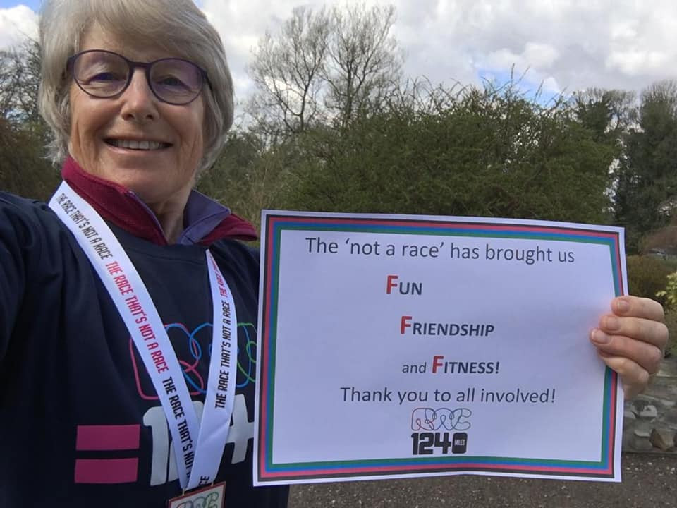 Linda is wearing her T-shirt and medal and hold a sign which says The race has brought us friendship, fun and fitness. Thank you to all involved!