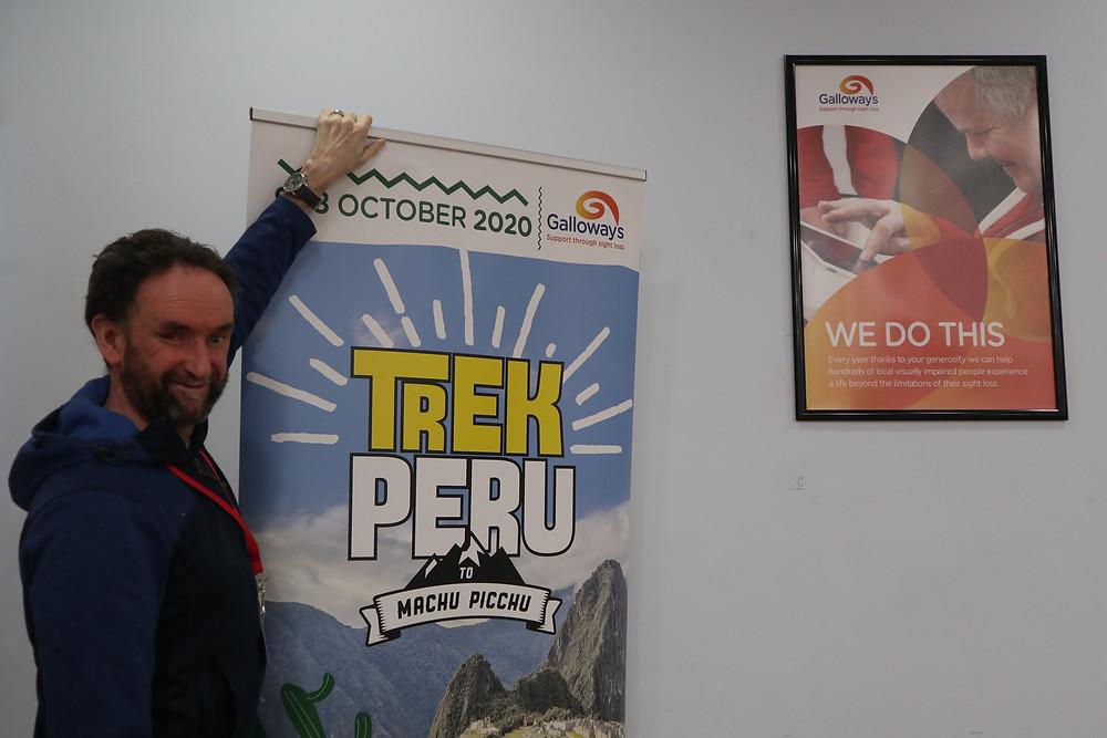 James Coulton stood next to the Trek Peru promotional banner