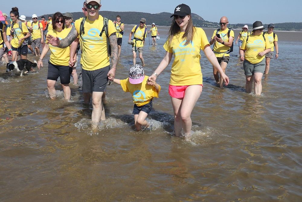 Photo shows a man and a woman in the foreground holding hands with a young child. Behind them is a group of other people, all paddling in the sea across Morecambe Bay. They are all wearing yellow Galloway's T-shirts