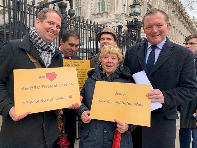 Representatives of the National Federation of the Blind of the UK and the British Deaf Association with Damian Collins MP outside 10 Downing Street, with posters which read:  'We love The BBC Teletext Service - Please do not switch it off' and 'Boris: Save the Red Button Now'