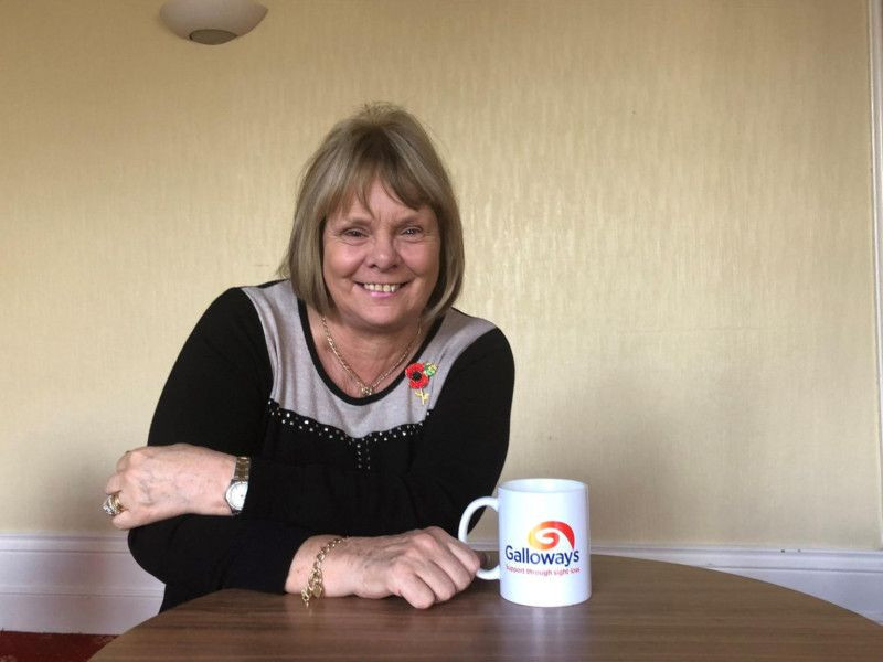 Photo shows Linda McCann smiling. She is sat at a table with a Galloway's mug
