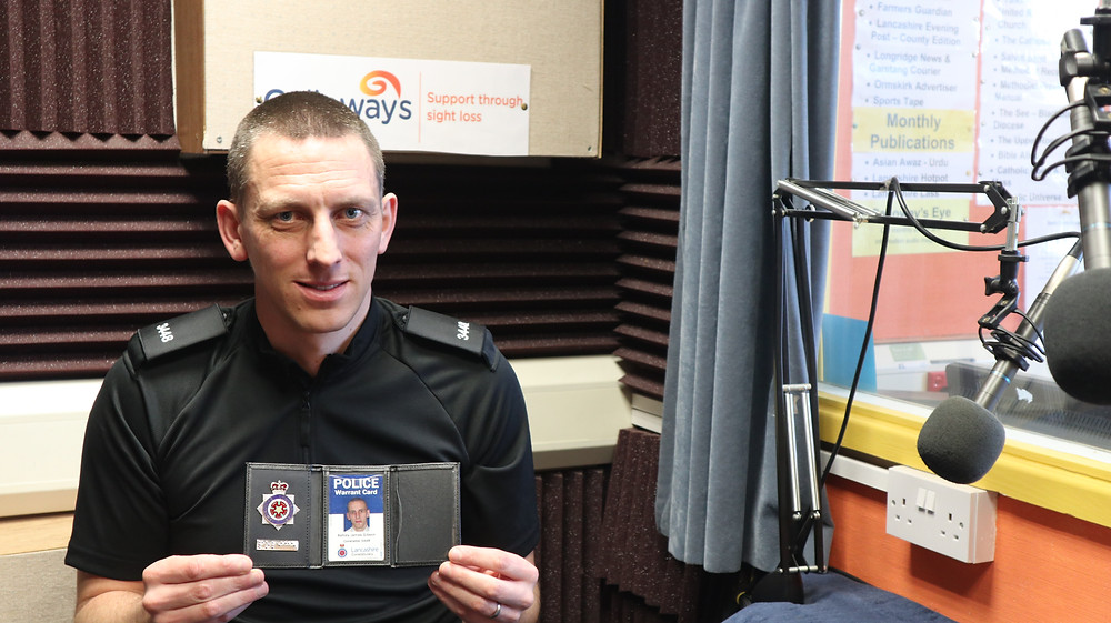 PC Ashley Gibson, from the Hate Crime Community Cohesion Unit at Lancashire Constabulary, holding his braille warrant card holder inside the Talking Newspaper studio at Galloway's