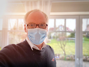 Photo shows a man wearing a disposable face mask and black rimmed glasses.