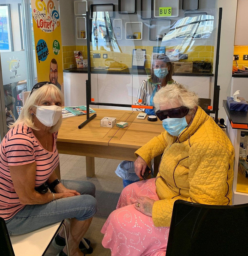 Photo shows sight loss advisor Pam behind a safety screen. In front are two women wearing face coverings