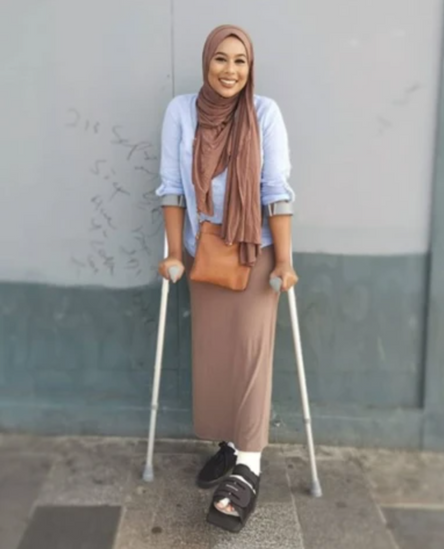 Woman stands in her hijab with crutches