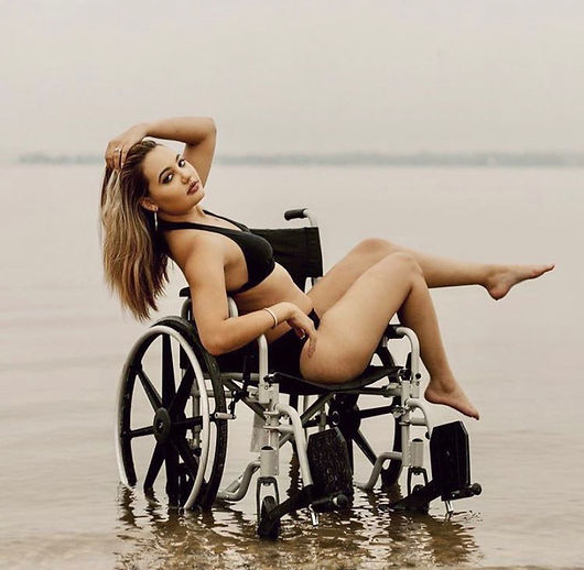 Woman in black bathing suite poses in shallow water in ther wheelchair with one hand in her hair.