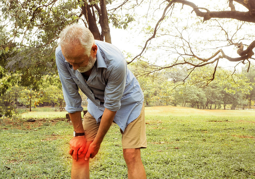 Aging man having pain in his knee on the