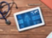 White tablet pc and doctor tools on wood