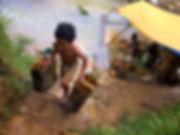 Exploitation familiale d'or avec les enfants qui transporte la terre et manipule le mercure