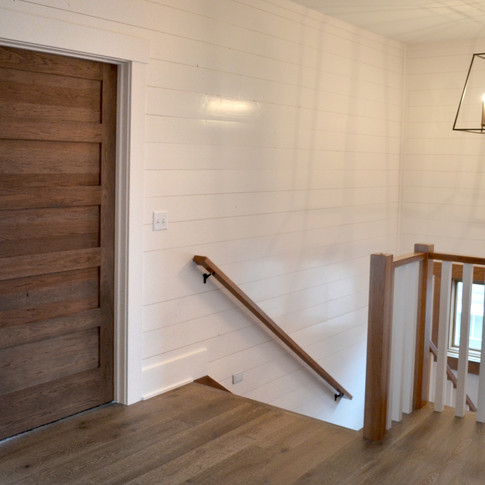 Shiplap walls and a Craftsman trimmed interior door at the top of a stairway.