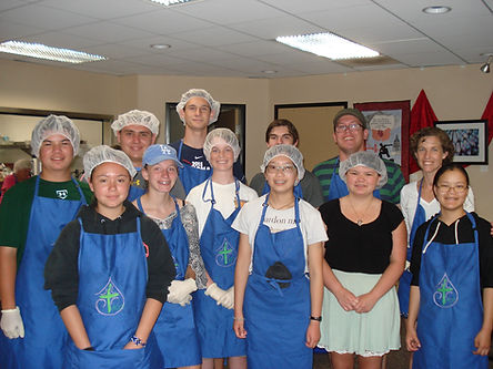12 young volunteers, many in blue aprons and clear caps