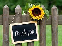 Brown fence, yellow sunflower, and thank you written on a chalkboard sign