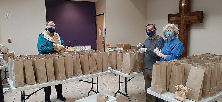 3 volunteers standing in a room next to tables filled with brown paper bags